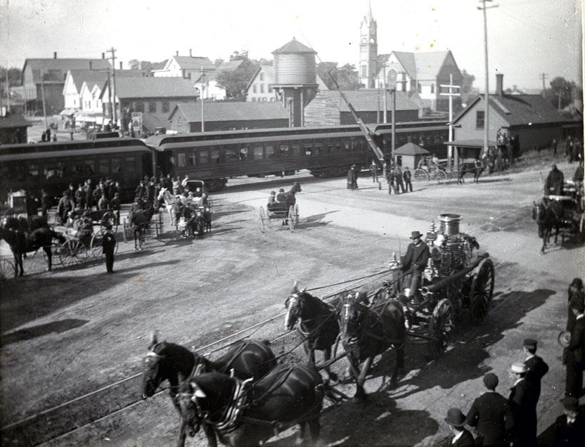 Black and White photograph of a horse drawn steamer and hose wagon going down old main street